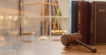Judge gavel with law books and scales of justice.