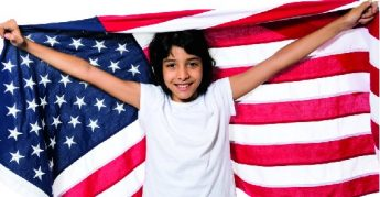 Young girl posing wrapped in the US flag in white background