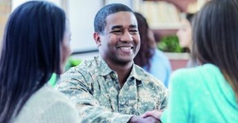 Smiling man in military uniform greeting 2 women.