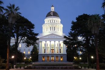 Sacramento Capitol Building at night, with trees to the right and left of the building.