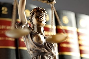 Lady justice holding balance scales in front of a book shelf full of law books
