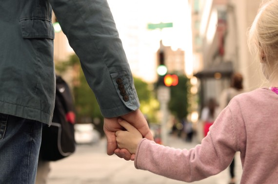 Parent holding the hand of young girl.