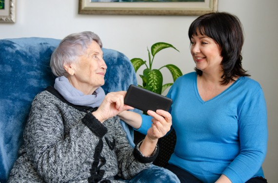 Caring volunteer came home to an elderly lady to teach her how to use a smartphone.